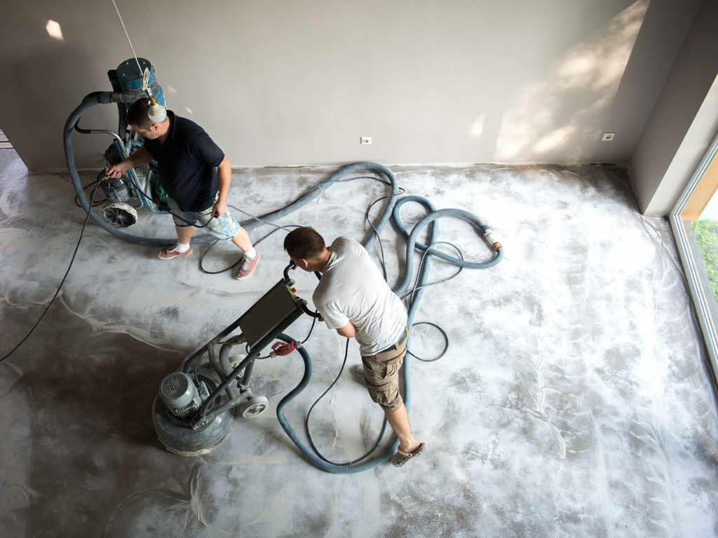 Construction worker in a family home living room that grind the concrete surface before applying epoxy flooring.Polyurethane and epoxy flooring.Concrete grinding.