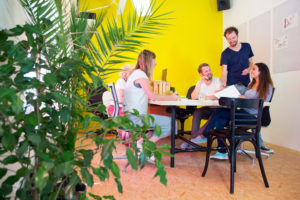 Designers, sitting in at a large table in a creative environment and office, surrounded by tack boards with drawings, plants and a repainted bright yellow wall